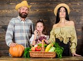 Family Farmers With Harvest Wooden Background. Parents And Daughter Celebrate Harvest Holiday Pumpki poster