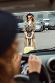 Cropped Image Of Woman Sitting At Steering Wheel While Stylish Female Tourist Standing With Wheeled  poster