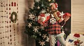 Santa Claus Man With Present Box At Christmas Tree. Christmas Man With Beard On Happy Face Hold Gift poster