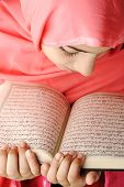 Adorable beautiful girl reading Koran