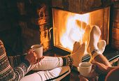 Couple In Love Drink A Tea Near Fireplace. Cozy Christmas Home Atmosphere poster