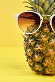 Juicy Ananas In Sunglasses. Fresh Tasty Pineapple In Sunglasses On Yellow Ackground, Cropped Image.  poster