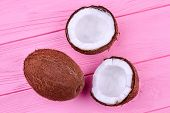 One Whole Coconut And Two Halves. One Whole And Two Cracked Coconut Halves On Pink Wooden Background poster