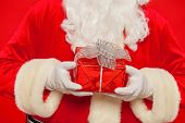 Photo Of Santa Claus Gloved Hand With Giftbox, On A Red Backgrou poster
