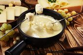 Gourmet Swiss Fondue Dinner On A Winter Evening With Assorted Cheese poster