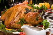 pic of turkey dinner  - Garnished roasted turkey on holiday decorated table with pumpkins and glasses of red wine - JPG