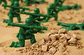 Miniature toy soldiers in desert battle scene.  Macro with shallow dof.