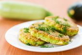 foto of zucchini  - fried zucchini fritters with dill on a plate - JPG