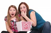 picture of watching movie  - two sisters one child and teen watching a movie with popcorn over white - JPG