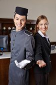 Concierge and receptionist in hotel offering welcome to guests