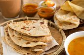 Indian food, Chapati flatbread, roti canai, dal, curry, teh tarik or pulled tea, acar. Famous indian