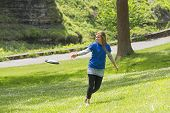 stock photo of frisbee  - Young Girl Playing Frisbee At The Park - JPG