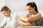 picture of sorrow  - Unhappy couple sitting on couch silently after argument - JPG
