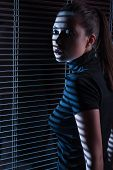 foto of jalousie  - Sexy woman in black dress with jalousie looking through the window with jalousie - JPG