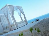 White four-poster bed standing outdoors with seascape view