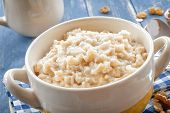 stock photo of cereal bowl  - Oatmeal with milk in a bowl on a wooden table - JPG