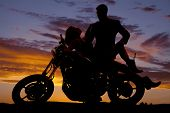 picture of motorcycle  - A silhouette of a woman laying back on the motorbike with her man looking down at her - JPG