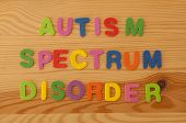 stock photo of autism  - Colourful foam letters spelling out Autism spectrum disorder on a wooden background - JPG