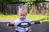 stock photo of tricycle  - Little blond boy sitting on a tricycle - JPG