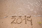 picture of happy new year 2013  - New Year 2014 is coming concept - inscription 2013 and 2014 on a beach sand, the wave is starting to cover the digits 2013 ** Note: Shallow depth of field - JPG