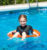 stock photo of lifeline  - cute  little girl swims in a wetsuit with a lifeline in the pool in  summer - JPG
