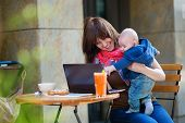 foto of internet-cafe  - Young working mother with her little son in a cafe - JPG