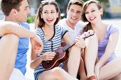 picture of ukulele  - Young woman playing ukulele friends - JPG