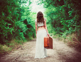 stock photo of girl walking away  - Young woman with suitcase in hand going away by a rural road