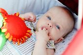 stock photo of finger-licking  - baby with fingers in mouth laying in stroller - JPG
