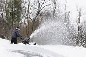 foto of snow shovel  - Snow being removed using snow blower during winter storm - JPG