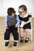 stock photo of lurex  - Little girl in black dress with mobile phone sitting on white chair next to boy with glasses and tablet computer - JPG