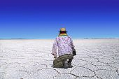 picture of kneeling  - Traveler with straw hat and scarf in bolivian national colors kneels at the desert of Uyuni Bolivia and looks at the wideness of the desert - JPG
