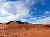 foto of saharan  - Red Saharan sand dunes in the Erg Chebbi desert of Morocco featuring foot trails in winter - JPG