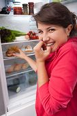 stock photo of greedy  - Young greedy girl reaching for the delicous donut in the fridge - JPG