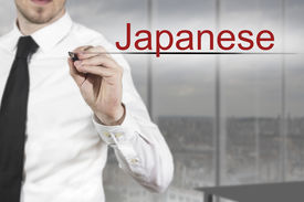 picture of pronunciation  - businessman in office writing japanese in the air - JPG