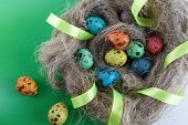 stock photo of quail egg  - Easter eggs in a nest made of linen with satin ribbon - JPG