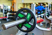 image of barbell  - Barbell holder in the gym. On the rear background man working out with barbell