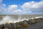 foto of dike  - Storm raging over a lake along a dike through Flevoland in spring - JPG