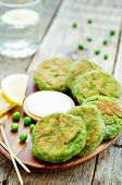 picture of yogurt  - fritters green peas with yogurt sauce and lemon on a dark wood background - JPG