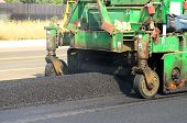 picture of paving  - Asphalt paving machine laying down a fresh layer of paving on a new road interchange project - JPG