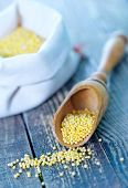 pic of millet  - raw millet in wooden spoon and on a table - JPG