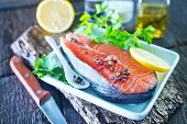 stock photo of redfish  - raw salmon with spice and lemon on the wooden board - JPG