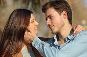 pic of flirt  - Couple in love looking each other ready to kiss in a park - JPG