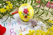 picture of decoupage  - Hand painted decoupage Easter egg on wooden surface with a Happy Easter card and two toy rabbit - JPG