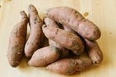 foto of batata  - pile of sweet potatoes on wooden background - JPG