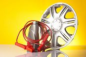 stock photo of alloy  - car accessories including alloy wheel and jump start cables - JPG