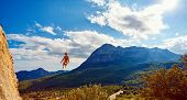 stock photo of mountain-climber  - female rock climber hanging on a rope near the rocky wall on the mountain background - JPG