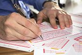 stock photo of lottery winners  - Man Marking on lottery ticket with a pen