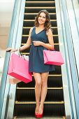 pic of escalator  - Full length of beautiful young woman standing on escalator and carrying shopping bags - JPG