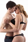 picture of caress  - Young half naked couple love play on the distance of a kiss guy in jeans caressing girl in black underwear studio shot white background - JPG